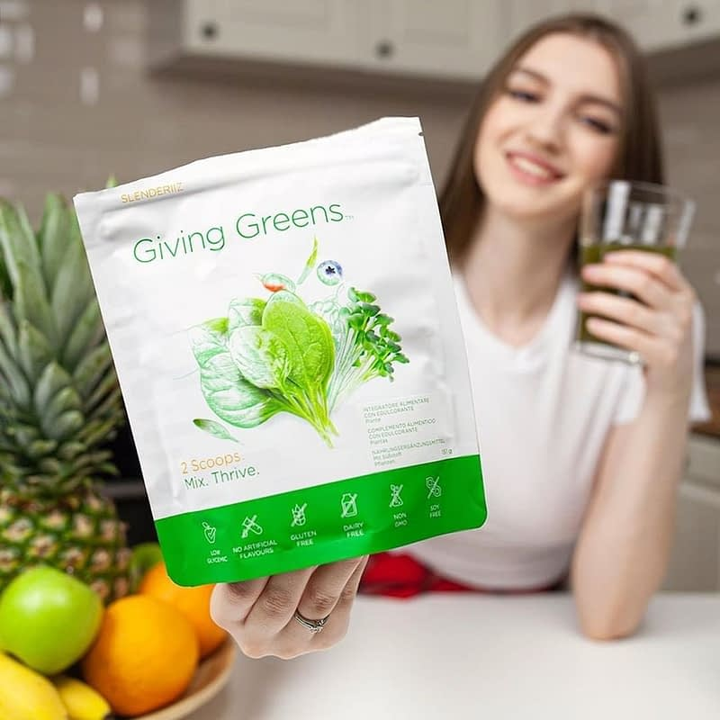young woman holding giving greens product and glass of giving greens powder mix