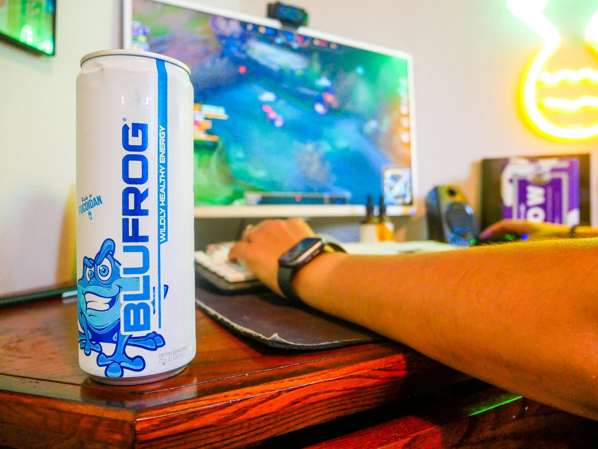 photo of blufrog energy drink on desk with gamer playing