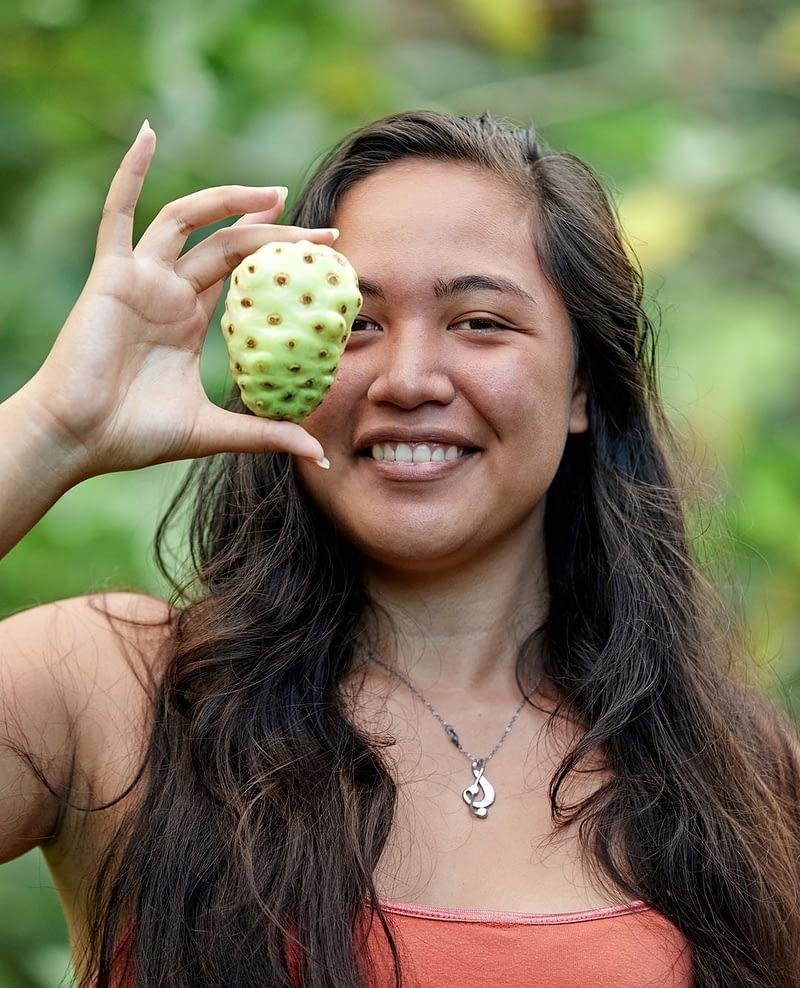 woman holding up Noni fruit